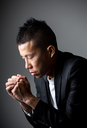 man praying: Young man praying Stock Photo