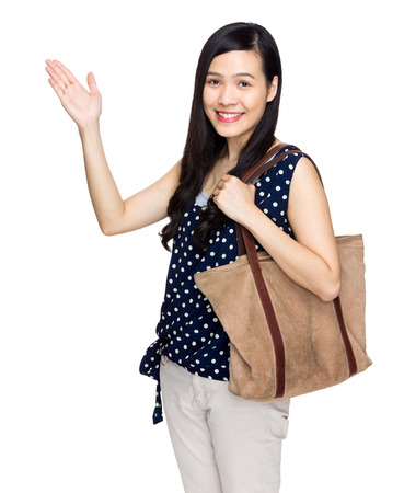 Asian woman with shoulder bag and hand present something