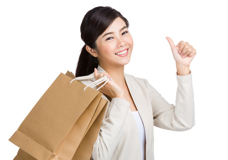 Asian woman thumb up and holding with paper bag photo