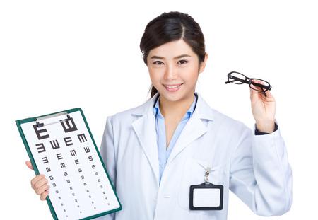 medical testing: Female doctor hold eyeglasses with eye chart  Stock Photo