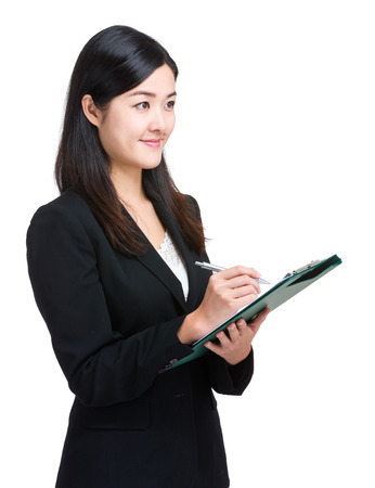 aside: Asian business woman take note on clipboard Stock Photo