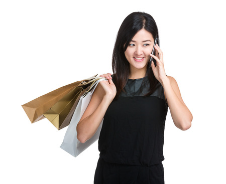 Shopping woman with paper bag and mobile phone photo