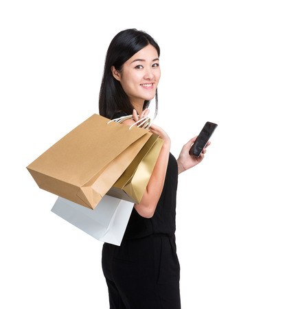 Woman with shopping bag and mobile phone photo