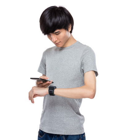 data synchronization: Data synchronization of smartphone and smartwatch in male hand Stock Photo