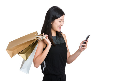 Asian young woman use mobile phone with shopping bag photo