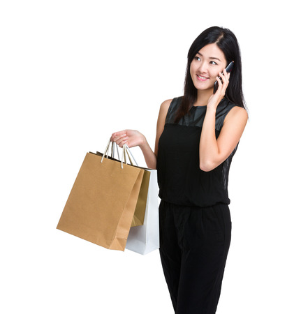Asian young woman talk on mobile phone with shopping bag photo