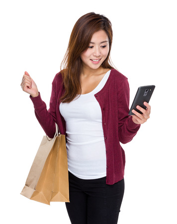 Girl with shopping bag and read the message of cellphone photo