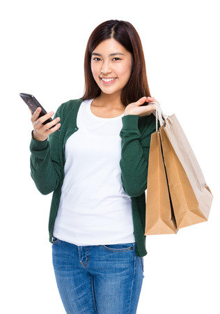 Young woman hold shopping bag and cellphone photo