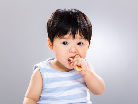asian flavors: Cute little boy eating cookie Stock Photo
