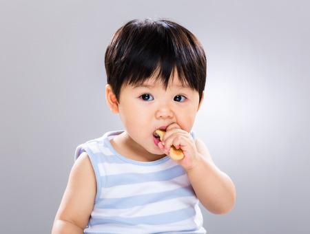 botanas: Niño lindo que come la galleta Foto de archivo