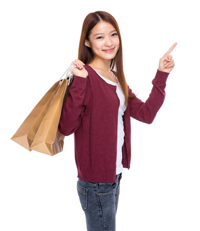 Asian young woman with shopping bag and finger up photo