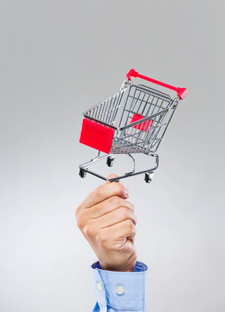 Businessman hold with small shopping cart photo