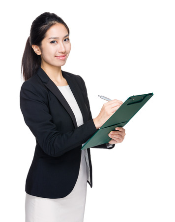 take down notice: Asian businesswoman write on clipboard Stock Photo