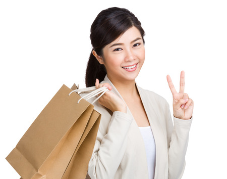 Happy girl with shopping bag and victory sign photo
