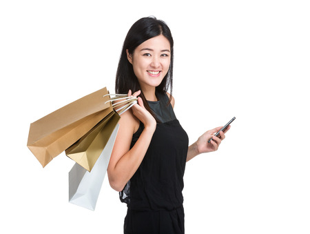 Happy shopping woman with paper bag and mobile phone photo