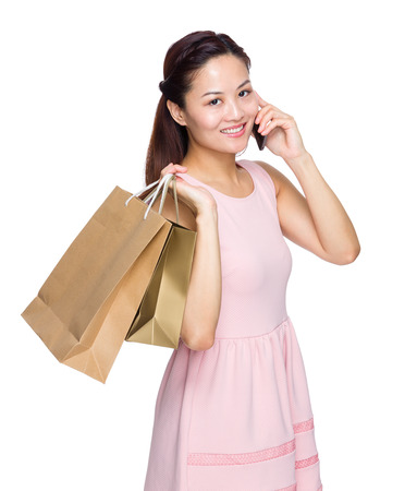 Woman with shopping bag and talk to mobile phone photo