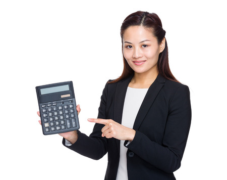 Businesswoman finger point up to a calculator photo