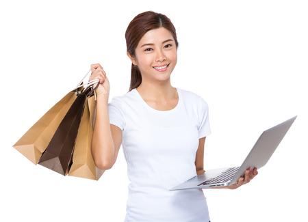 chicas compras: Uso Woman portátil y bolsa de la compra Foto de archivo