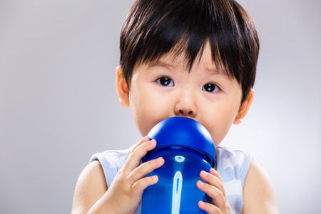Baby boy drink with water bottle close up photo