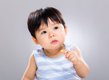 Asian baby boy eat cookie photo
