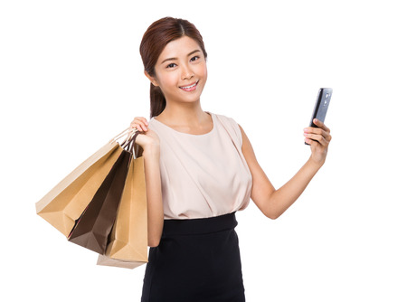 Happy woman with shopping bag and mobile phone photo