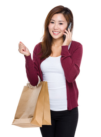 Young woman hold shopping bag and talk to mobile photo
