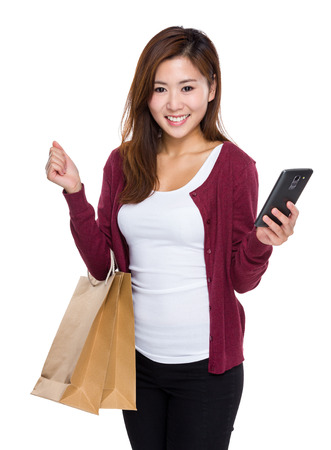 Young woman hold shopping bag and mobile phone photo