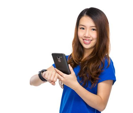 sincronizacion: Uso de la mujer del tel�fono m�vil de sincronizaci�n a reloj port�til Foto de archivo