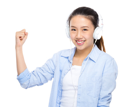 clench: Asian young woman listen to music with headphone and arm clench