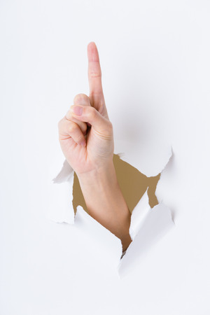 breaking through: Woman hand breaking through paper wall with finger point up