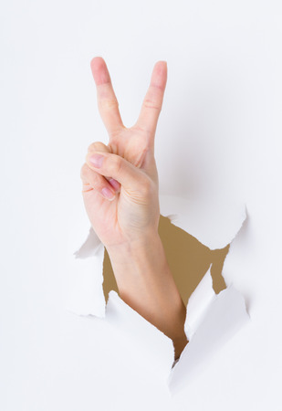 to break through: Woman hand breaking through paper wall pointing with the two finger Stock Photo