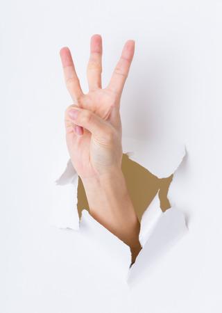 breaking through: Three finger breaking through paper wall Stock Photo