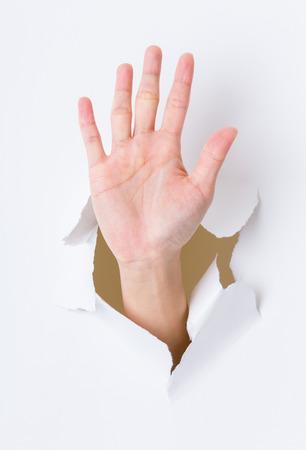 breaking through: Hand palm breaking through paper wall