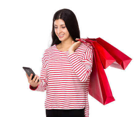 Woman hold with shopping bag and look at cellphone photo