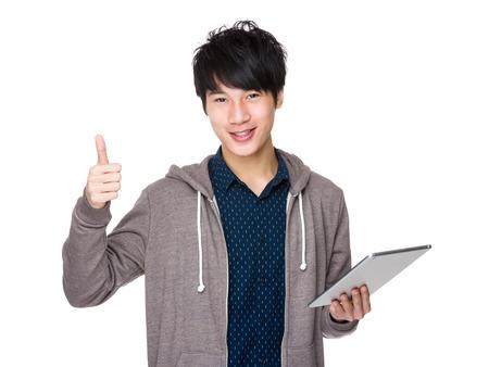 colegios: Asia uso hombre guapo de la tableta y el pulgar arriba Foto de archivo