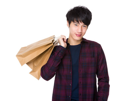 Young Asian man shopping and holding bags Stock Photo