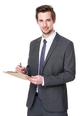 Businessman takes notes on clipboard photo