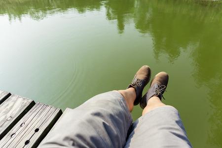 piernas hombre: Piernas del hombre que se sientan en camino de madera