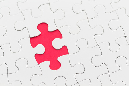 missing piece: Jigsaw puzzle with missing piece over red background Stock Photo
