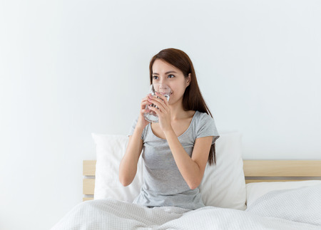 sit down: Mujer de agua potable en la cama