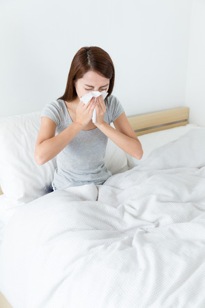 runny: Woman runny nose on the bed