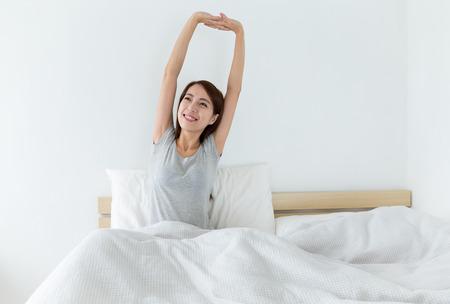 despertar: Mujer joven que despierta feliz, después de una buena noche de sueño Foto de archivo