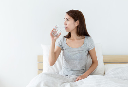 houses on water: Woman drink a glass of water at morning Stock Photo