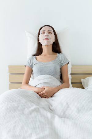 woman lying down: Woman lying down on bed and do masking Stock Photo