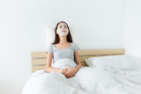Woman sleeping on bed and do masking Stock Photo
