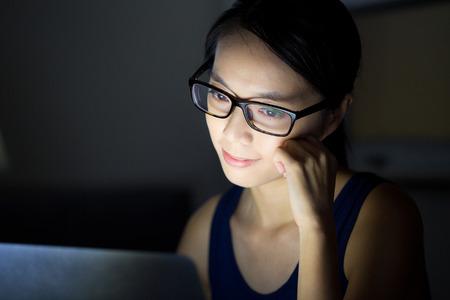 Mulher com óculos e olha para computador à noite