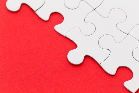 missing link: Jigsaw puzzle on red paper Stock Photo