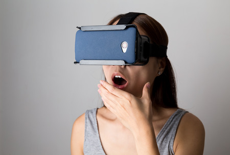 though: Excited woman watching though the VR device