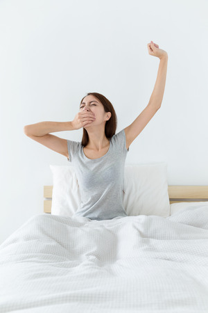 Asian woman just wake up , yawning and hand raised up