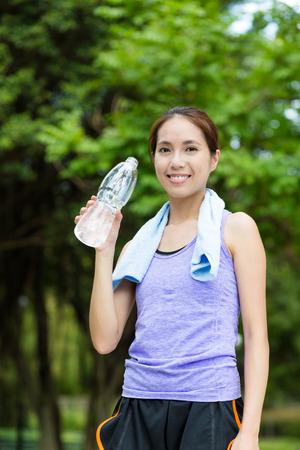 take a break: Sporty woman take a break and holding a bottle of water